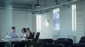In the empty hall three staff at the table look the paper and talk. Two beautiful young women and a man dressed in office attire sitting behind a desk and stock video footage