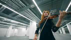 Empty hall and a woman in black dress playing the violin. 4K stock video footage