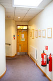Empty hallway with door. Empty hallway with closed door and fire extinguishers Stock Photo