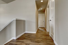 Empty hallway with hardwood floor, beige walls and staircase Royalty Free Stock Images