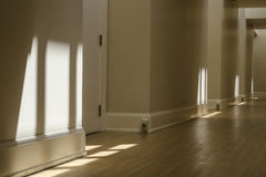Empty hallway. A long hallway disappears into the distance as sun filters down in patterns from the skylights above Royalty Free Stock Photography