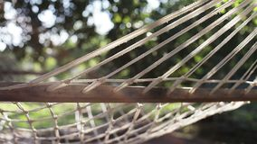 An empty hammock in the end of summer. Slow motion. Sun glare. Lens flare stock footage