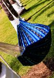 Empty hammock hangs in the garden for relaxation in summer. royalty free stock images
