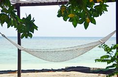 Beachfront hammock facing blue ocean on beach tropical island. An empty hammock happily swings on the white sandy beach of a beachfront bungalow, facing the Stock Photography