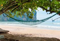 An empty hammock in the shade of a tree on the Andaman Sea. Beach royalty free stock photography