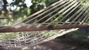An empty hammock swings in the wind. Slow motion. Sun glare. Lens flare stock video footage