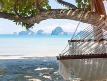 Empty hammock on the tropical beach with trees and beautiful sea. View background. Holiday and travel concept Stock Photography