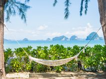 Empty hammock on the tropical beach with trees and beautiful sea. View background Royalty Free Stock Image
