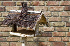 Empty handmade bird house. In front of brick wall stock image