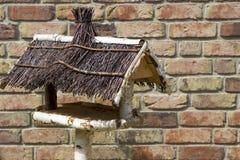 Empty handmade bird house. In front of brick wall Stock Image