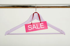Empty hanger on a rack of clothes with the sale sign. Stock Images