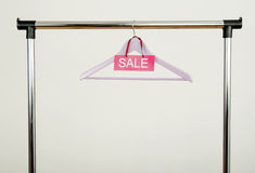 Empty hanger on a rack of clothes with the sale sign. Stock Photography