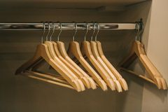 Empty hangers hang in a row in the closet.  stock photos