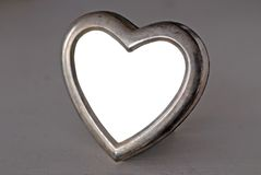 Empty Heart Shaped Photo Frame. An old photo frame with a distressed chrome rim on a white wooden tabletop, no picture in frame Stock Image