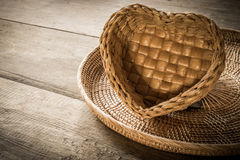 Empty a heart-shaped rattan basket and tray on wooden background Stock Photos