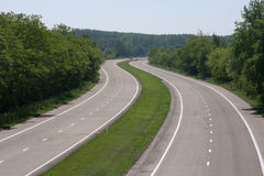 Empty highway. Highway through the forest with empty lanes Royalty Free Stock Image