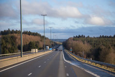 Empty Highway. Cars driving on almost empty highway with cloudy sky stock photo