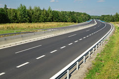 Empty highway disappearing into the trees in the forest Royalty Free Stock Photography