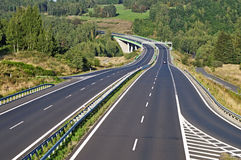 Empty highway between forests in the landscape Stock Images