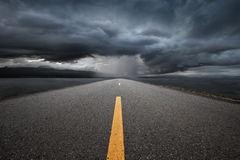Empty highway leading to the mountains through the rain. Empty highway leading to the mountains through the rain on a background of dark storm clouds Royalty Free Stock Photography