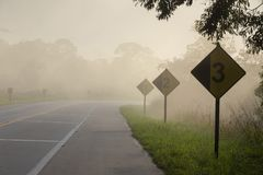 Empty highway in morning mist with warning signs stock image