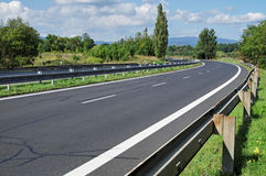 Empty highway passing landscape trees Royalty Free Stock Photo