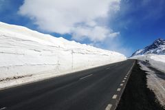 An empty highway and snow covered landscape next to it in St Moritz Switzerland in the alps.  Royalty Free Stock Image
