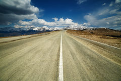Empty highway to the mountains Stock Photo
