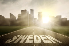 Empty highway with word of Sweden at sunrise Stock Photo