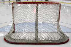Hockey Net. The back view after the ice was done. Reflection of the ceiling lights are on the ice. The goalie's crease is painted in blue. The Net posts are red Stock Images
