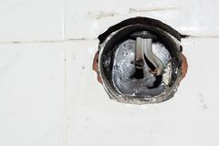 Empty hole for electric socket with damaged wires Royalty Free Stock Photography