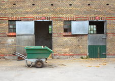 Empty horse stables with dirt wagon on asphalt Royalty Free Stock Photo