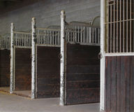 Empty horse stalls inside a building. Stock Images