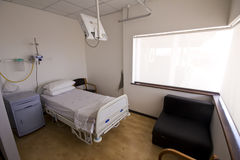 Empty hospital bed in room with couch Stock Photo