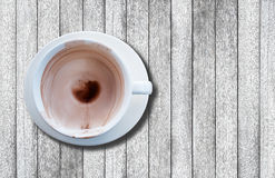 Empty hot beverage(coffee, chocolate, etc.), with dregs in cup and stained, on wood background with copyspace Royalty Free Stock Photography