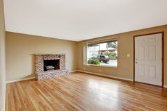 Empty house interior. Living room with fireplace. Emtpy house inteiror. Living room with brick fireplace and entrance door view royalty free stock photo