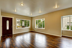 Empty house interior. Spacious living room with new hardwood flo. Or and ivory walls Royalty Free Stock Images