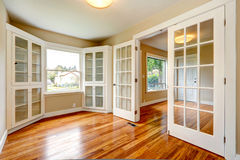 Empty house interior. View of entrance hallway and office room. Emtpy house with new hardwood floor and white french doors. View of entrance hallway and small Royalty Free Stock Photography