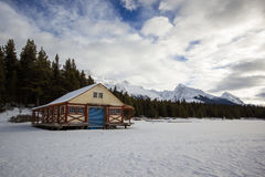 Empty hut and boat dock on winter frozen lake in high mountains, maligne lake, jasper nation park, Canada Stock Image