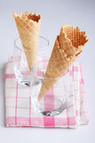 Empty ice cream cones in clear glasses on pink fabric Royalty Free Stock Image