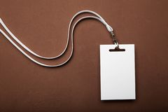 An empty identification card, name tag of an employee or visitor with a vintage strap on a brown background stock photo