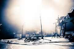 Empty illuminated stage. With drumkit, guitar and microphones royalty free stock photo