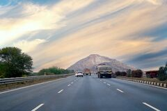 Free Empty Indian Highway With Trucks And Cars With Long Straight Road Leading To Mountain In Distance Royalty Free Stock Photography - 177965757