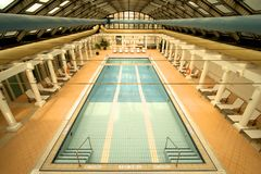 Empty indoor swimming pool with sun loungers Royalty Free Stock Photo