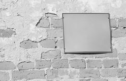 Empty information sign on old brick wall in black and white. Blank information sign on an old brick wall in black and white Royalty Free Stock Photography