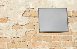 Empty information sign on old brick wall. Blank information sign on an old orange brick wall Royalty Free Stock Image
