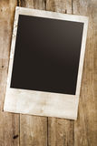 Empty instant paper photo of  camera on wood table Royalty Free Stock Image