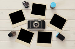 Empty instant photographs next to old camera and film rolls Stock Image