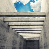 Empty interior with concrete walls, beams and cloudy sky. Abstract architecture background, empty interior with concrete walls, beams and cloudy sky outside Stock Photo