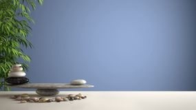 Empty interior design feng shui concept zen idea, white table or shelf with pebble balance and green bamboo, over blue background. Copy space royalty free stock photos